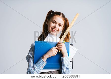 smiling teenager girl with two tails holding pointer and folder with papers in hands, isolated