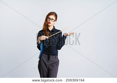 red-haired beautiful girl in glasses and red lipstick holds pointer and angrily looks at camera, isolated