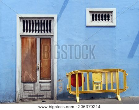 derelict abandoned boarded up blue house with white broken door bars ans plastic yellow barrier in the street