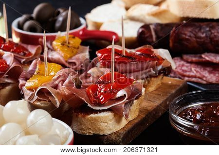 Spanish Tapas With Slices Jamon Serrano And Grilled Pepper. Also Olives, Salami, Pickled Onions, And