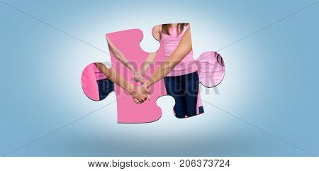 Mid section of women in pink outfits holding hands while standing for breast cancer awareness against blue background