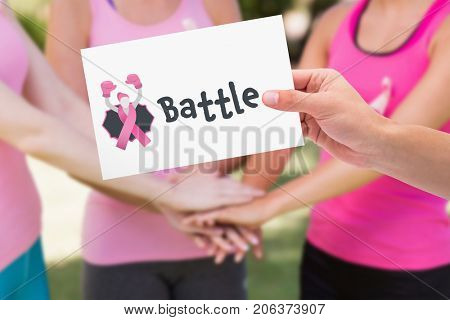 Hand holding card against mid section of female volunteers stacking hands