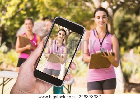 Hand holding mobile phone against white background against female volunteer writing in clipboard
