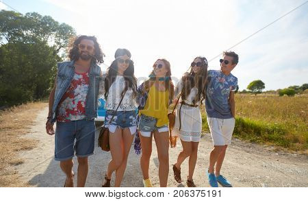 summer holidays, trip, travel and people concept - smiling happy young hippie friends at minivan car walking along road