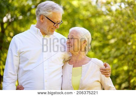 old age, retirement and people concept - happy senior couple hugging at summer park