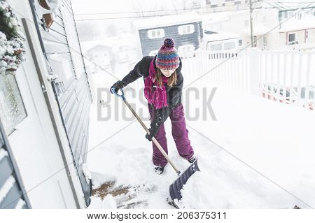 A woman shoveling and removing snow outside