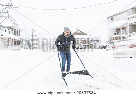 a man cleans snow with his shovel in winter season