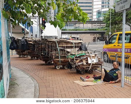 HONG KONG ASIA - SEPTEMBER 20 2017; Cardboard recycling collector takes a break and falls asleep on footpath on a busy Central city intersection with his handcarts of stacked flattened cardboard boxes.