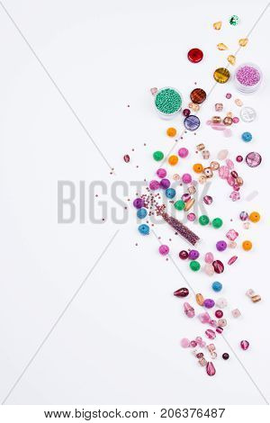 Bead mix. Glass seed beads and felted beads for jewelrymaking on white background. Hobby handmade fine arts. Top view.