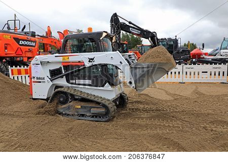 HYVINKAA FINLAND - SEPTEMBER 8 2017: Operator moves buckets of sand in a work demo with Bobcat T450 Compact Track Loader on Maxpo 2017.