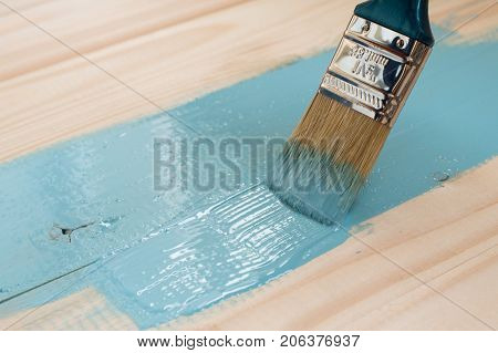 worker paints board. the employee paints the a wooden table. worker paints wooden board. wooden background with copy space
