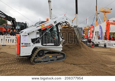 HYVINKAA FINLAND - SEPTEMBER 8 2017: Operator works with Bobcat T450 Compact Track Loader on sand work site on Maxpo 2017.