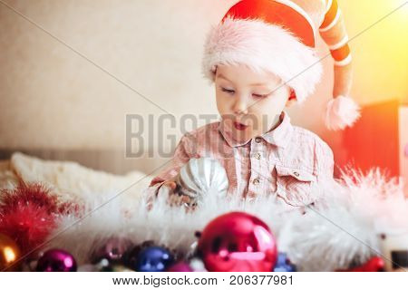 Cute Child In Gnome Hat Surprised Looking On A Christmas Tree Decorations, At Home