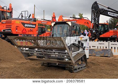 HYVINKAA FINLAND - SEPTEMBER 8 2017: Operator works with land leveler mounted on Bobcat T450 Compact Track Loader on a sand work site on Maxpo 2017.