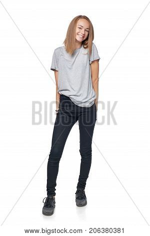 Teen girl in full length standing smiling at camera shrugging her shoulders, isolated on white background