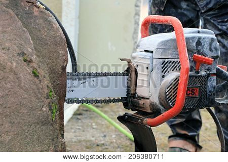 HYVINKAA FINLAND - SEPTEMBER 8 2017: Detail of ICS chain saw with the blade inside granite stone during a professional work demo on Maxpo 2017.