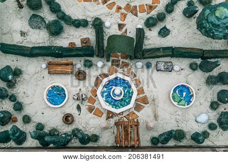 Sand therapy. Top view of toy miniature trees and small elements of landscape in a sand box. Anti-stress psychological rehabilitation therapy