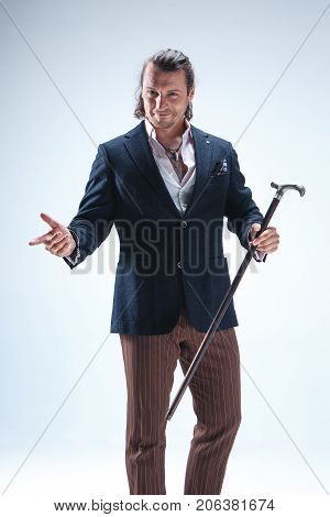 The mature bearded man in a suit holding cane. Isolated on a blue studio background.