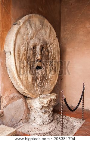 The Mouth of Truth (La Bocca della Verita) carved from Pavonazzo marble in the portico of the church of Santa Maria in Cosmedin in Rome Italy