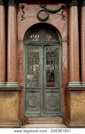 Old ornate iron door. Entrance to an old tomb crypt at a cemetery.