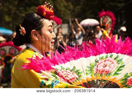 Khabarovsk Russia - August 13 2017: Korean traditional dancer. Old lady wearing colorful yellow and pink dress dancing Buchaechum or fan dance