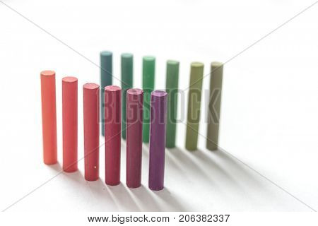 Close up of bunch standing colorful pastel chalks with color gradation, blurred effect, over white background