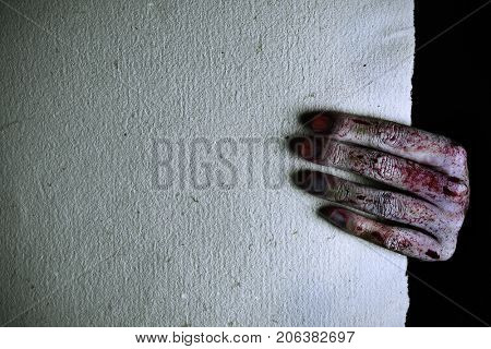 closeup of a scary and bloody hand holding a textured paper with a blank space on the left