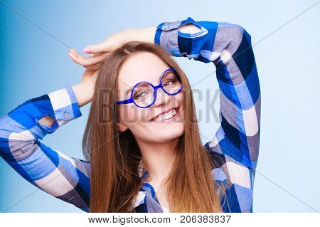 Studying education and fun concept. Happy smiling nerdy woman in weird big glasses. Studio shot on blue background