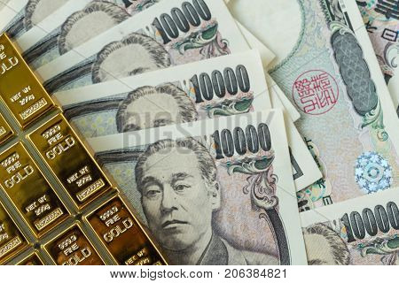 gold bullion ingot and pile of japanese yen banknotes as financial safe haven or investment concept.