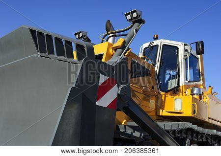 Bulldozer, huge yellow powerful construction machine with big scoop and grey tracks, heavy industry, bottom view, blue sky on background