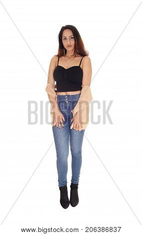 A beautiful young woman standing in jeans and a black corset with brunette hair isolated for white background