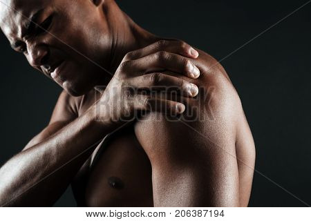 Cropped photo of young shirtless afro american man with shoulder pain, isolated on black background