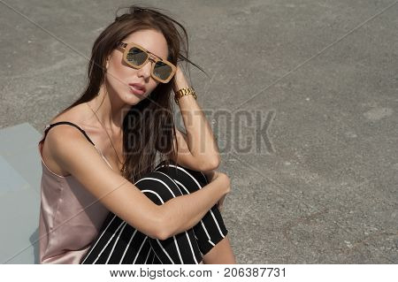 Outdoor Portrait Of A Young Beautiful Fashionable Happy Lady Wearing Sunglasses, In A Wooden Frame.