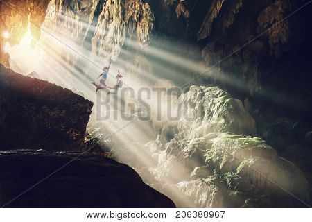 Lover women and men asians travel relax in the holiday. Jump cliff in the cave inside stalagmite caves in Asia Laos