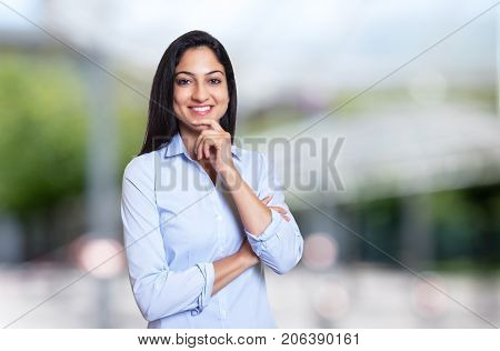 Laughing arabic businesswoman looking at camera outdoor in front of an office building