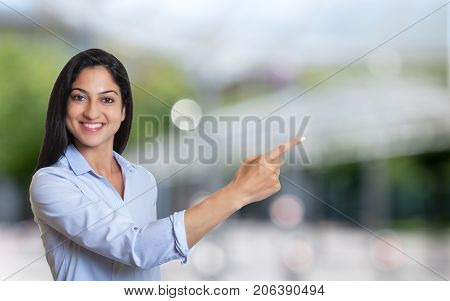 Laughing arabic businesswoman pointing sideways outdoor in front of an office building