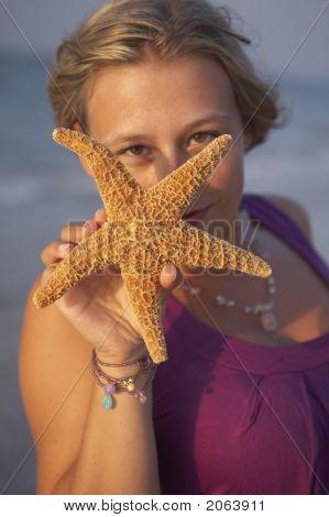 Cute Girl Is Holding Up An Seastar