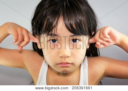 Defying and Stubborn Child with Fingers in the Ear