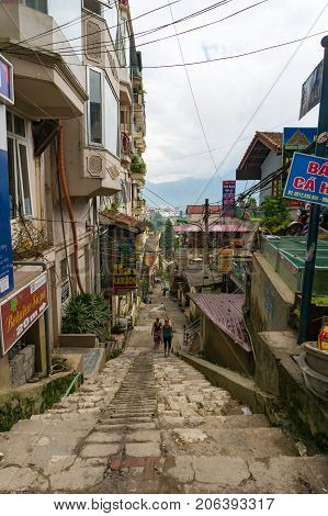 Two Tourists Climbing The Stairs On One Of The Streets In Sapa Town