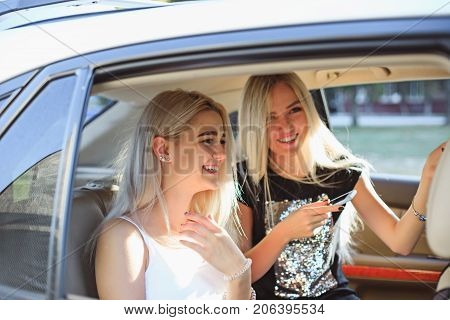The pretty european girls 25-30 years old in the car making photo on mobile phone