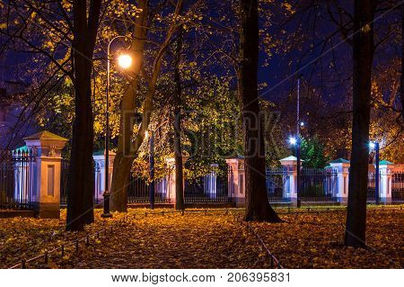Night autumn view of illuminated alley and fence in Nikolskiy garden St. Petersburg Russia