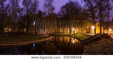 Dusk panoramic autumn view of park pond and building of State University of Communication in Yusupov Garden Saint Petersburg Russia
