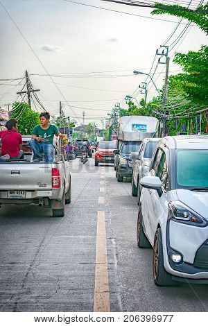 BANGKOK THAILAND - AUGUST 01: Traffic backs up as two unidentified male sits on a the bed of a pickup truck moving in the opposite direction on August 01 2017 in Bangkok.