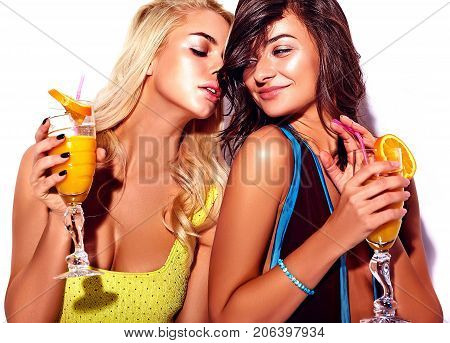 Two trendy hipster girls blonde and brunette models drink cocktails in colorful swimwear on white background