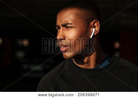 Close up portrait of a young afro american man with earphones looking away