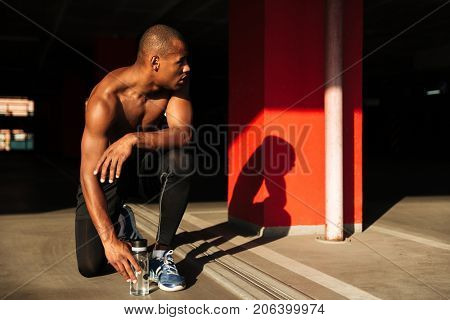 Portrait of a fit muscular half naked african sportsman sitting on his knee and resting indoors