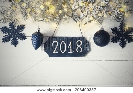 Black Chirstmas Plate With Text 2018 For Happy New Year Greetings. Fir Branch With Fairy Lights On Wooden Background. Black Christmas Decoration Like Balls And Snowflakes.