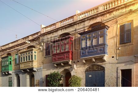 Street with traditional colorful balconies in Malta. Typical historical architecture of medieval Malta