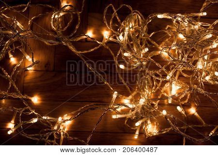 Christmas background with festive decoration - Christmas glowing lights garland on a old antique wooden parquet floor sparkling garland for greeting card. Christmas background with festive decoration