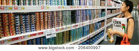 BANGKOK THAILAND - AUGUST 05: An unidentified woman shops in the canned food section of Macro superstore on August 05 2017 in Bangkok.
